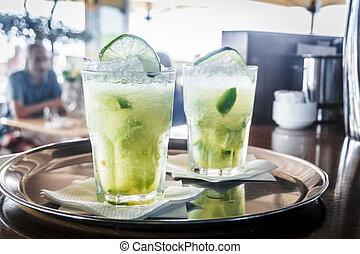 Two caipirinha cocktails on a bar counter