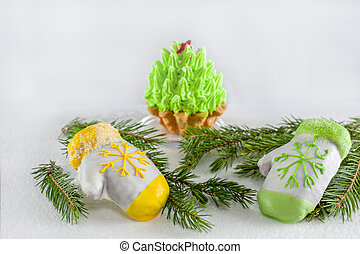 Two cakes in the form of mittens lying on the green branches of a Christmas tree for Christmas. Copy space. Close-up.
