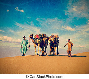 Two cameleers in dunes of Thar deser