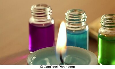 Two candles burn, few open bottles with color aroma oil and sea star lay on table, closeup in motion
