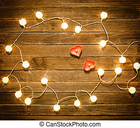 Two candles in the shape of heart among the glowing lanterns made of rattan on a wooden background. View from above, space for text