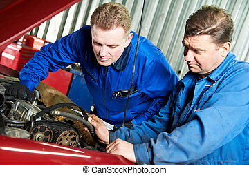 two car mechanic diagnosing auto engine problem - two motor...