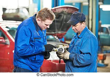 two car mechanic diagnosing auto engine problem