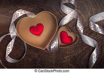 Two cardboard hearts with red hearts inside and white ribbon on a wooden background. Valentine's day.
