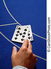 Two cards in hand on a Casino table - Two poker or baccarat...