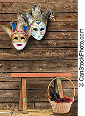 Two carnival masks hanging on the wall at the bottom of a wooden bench
