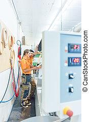 Two carpenters cleaning veneer machine in workshop