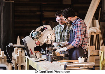 Two carpenters cutting wooden plank with a circular saw