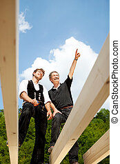 Two carpenters discussing the work on the roof