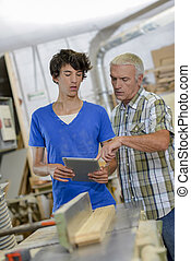 Two carpenters looking at screen of tablet