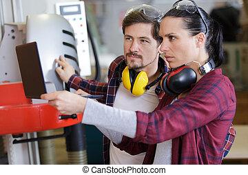 two carpenters operating a machine