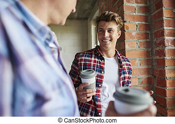 Two carpenters taking a quick coffee break