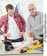 two carpenters working in office, one with screwdriver