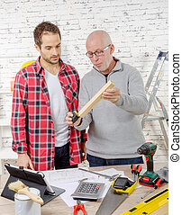 two carpenters working in their office
