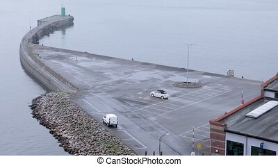 Two cars on parking at small promontory in port, view from...