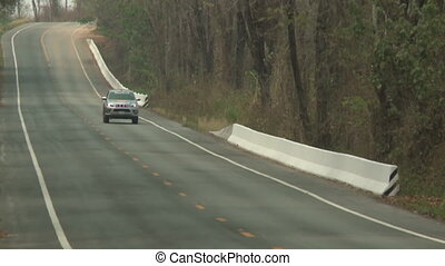 Two cars traveling on a mountain road