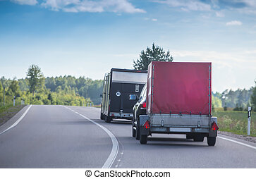 two cars with trailers on road