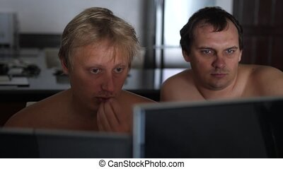 Two casual young men friends with bare chest at home sharing information and using computer