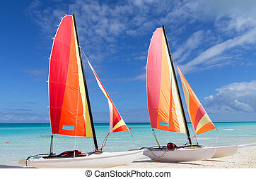 Two catamarans with its colorful sails wide open on cayo Santa Maria Cuban white sandy beach