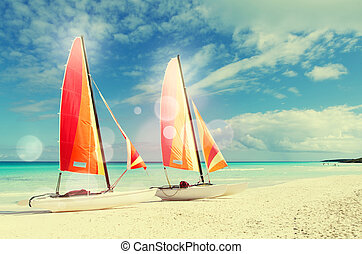 Two catamarans with its colorful sails wide open on Cuban white sandy beach with retro effect applied