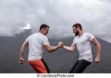 Two caucasian athletes in sportive wear measuring forces at outdoor training