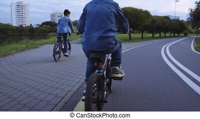 Two caucasian boys in denim clothes ride bicycle.