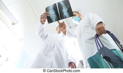 Two caucasian doctors view mri picture and discussing about it. Medical workers in hospital examine x-ray prints. Male medics consult with each other while looking at x ray image. Low angle of view