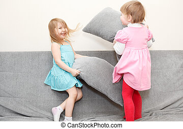 Two Caucasian happy playful little girls in pillows fighting on sofa