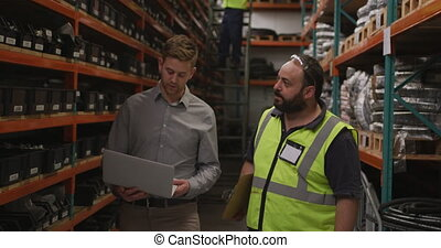 Two Caucasian male factory workers at a factory making ...