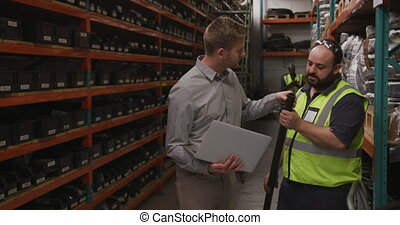 Two Caucasian male factory workers at a factory making hydraulic equipment, one wearing vis vest and holding a pipe, standing in warehouse, in discussion, another holding a computer laptop, in background another coworker, in slow motion.