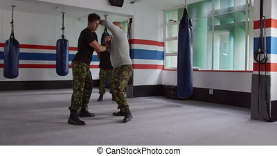 Two caucasian men learning self defense from trainer in gym...