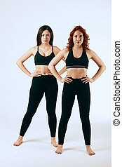 Two caucasian women are stand together in black tank tops and leggings on white