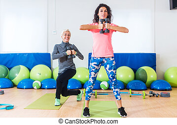 Two Caucasian women doing exercises with dumbbells working...