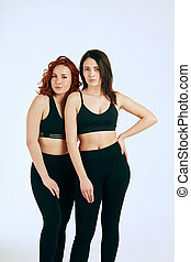 Two caucasian women standing together in black tank tops and leggings on white