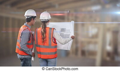 Two Caucasian workers wearing an orange high vest and hat checking their plan and pointing fingers