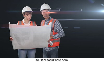 Two Caucasian workers wearing an orange high vest and hat holding a plan in a dark background