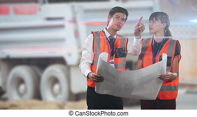 Animation of Caucasian male and female architect wearing hi vis vests holding plans, discussing and pointing to an industrial warehouse space, a truck in the background, digital composite