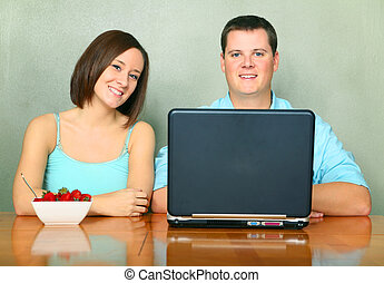 Two Caucasian Young Adults Sit On Kitchen Table With Laptop