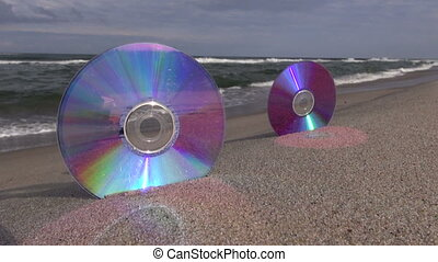 Two CDs on sea beach and waves