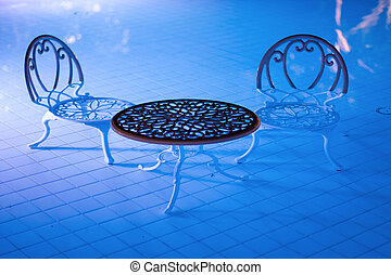 Two chairs and a table stand in the pool