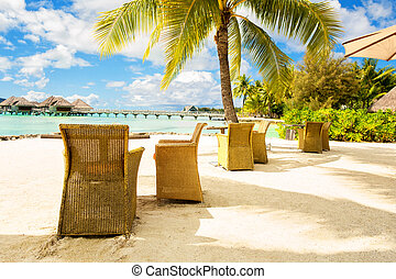 Two chairs and on a sand beach with a view on the lagoon and Mount Otemanu on the tropical island of Bora Bora, near Tahiti, in French Polynesia.