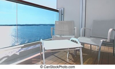 Two chairs and table at balcony on ship which floats in sea
