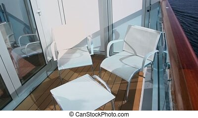 Two chairs and table at balcony on vessel which floats in sea