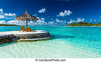 Two chairs and umbrella on a jetty on a tropical island