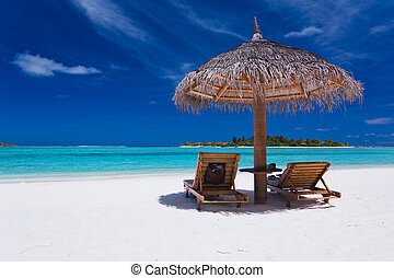 Two chairs and umbrella on stunning beach