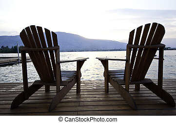 Two lounge chairs on a deck by the lake in the setting sun.