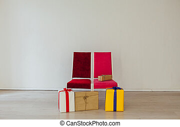 two chairs with birthday gifts at the white wall