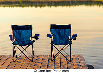 two chairs without people on a wooden pier near the lake at dawn