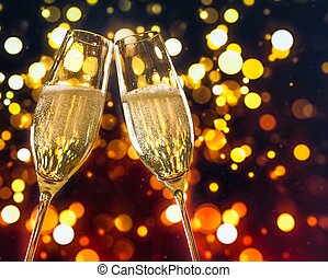 two champagne flutes with golden bubbles on colorful light bokeh background