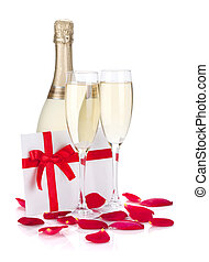 Two champagne glasses, letter and rose petals